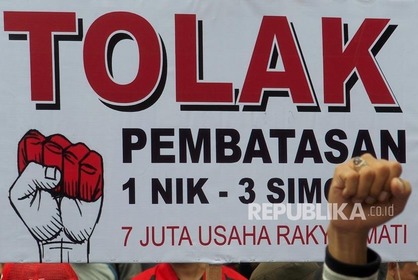 Pengunjuk rasa yang tergabung dalam Kesatuan Niaga Celluler Indonesia (KNCI) membentangkan spanduk dan poster, saat berunjuk rasa menolak pembatasan registrasi kartu prabayar telepon seluler satu NIK untuk tiga kartu.