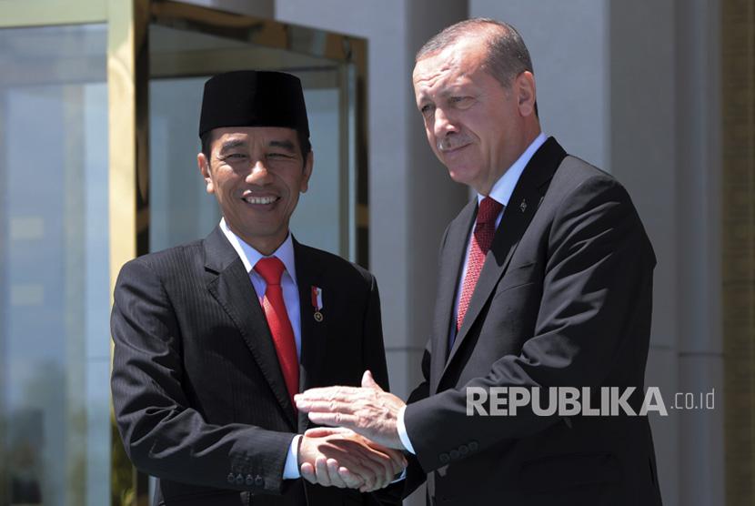 Presiden Turki Recep Tayyip Erdogan dan Presiden Indonesia Joko Widodo berjabat tangan saat upacara penyambutan di istana kepresidenan di Ankara, Turki, Kamis, (6/7).