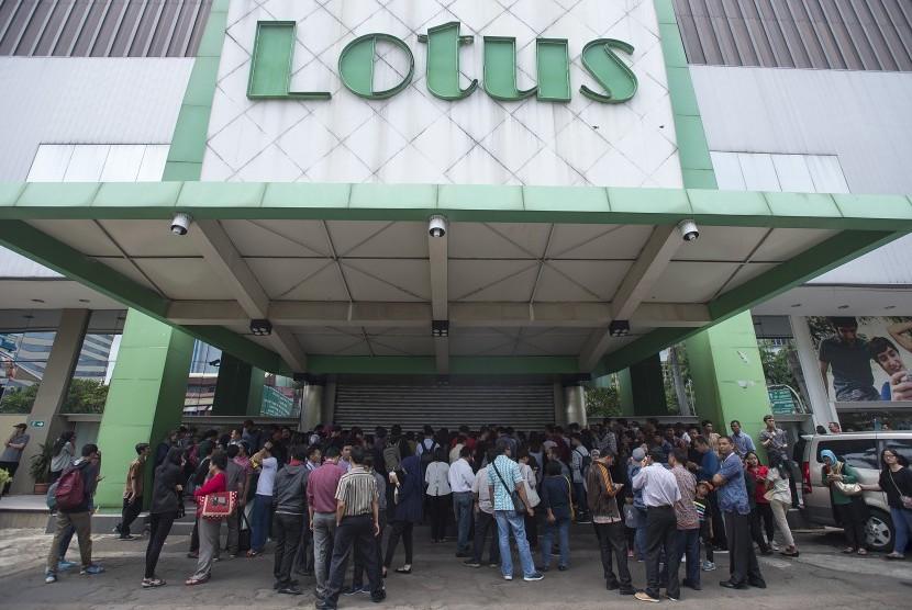 Sejumlah calon pembeli berdiri mengantre di depan pintu masuk pusat perbelanjaan Lotus yang masih tertutup untuk berbelanja barang dengan potongan harga di Jalan K.H. Wahid Hasyim, Jakarta Pusat, Rabu (25/10).