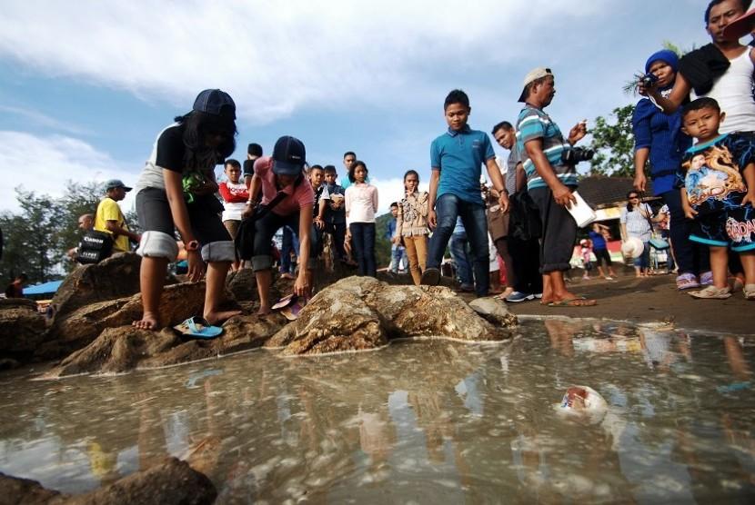 Sejumlah pengunjung berada di dekat batu Malin Kundang yang terendam air laut, di Pantai Air Manis, Padang, Sumatera Barat, Sabtu (3/1)