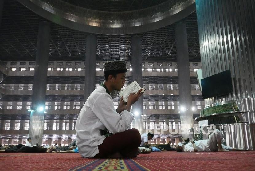 Seorang jamaah laki-laki sedang membaca ayat-ayat suci Alquran di Masjid Istiqlal Jakarta, Senin (6/6).(Republika/Darmawan)