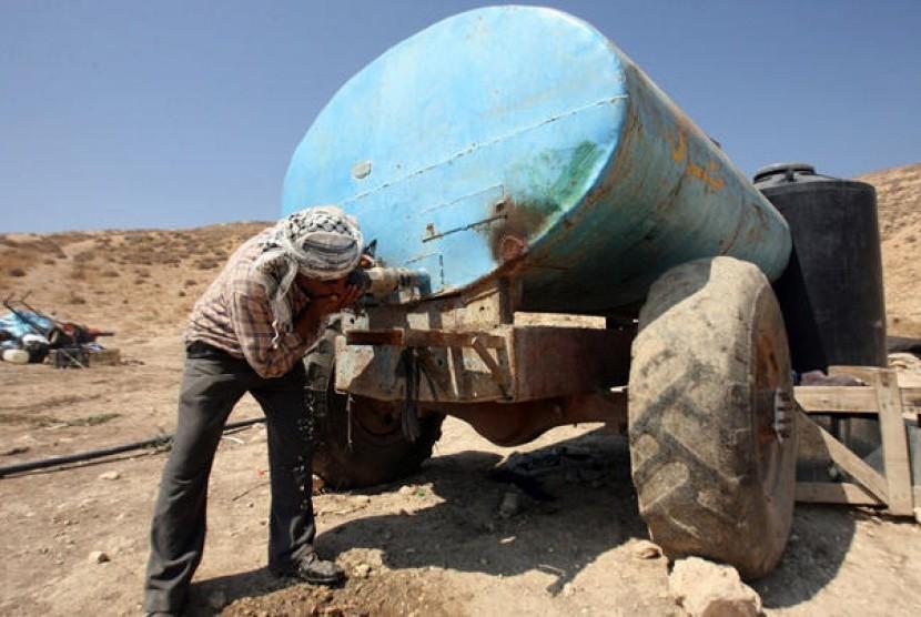 Seorang warga Palestina  yang tinggal di Area C, Tepi Barat, meminum air langsung dari tangki penyimpanan air. Israel membatasi bahkan meniadakan akses ke sumber-sumber alam untuk warga Palestina di kawasan tersebut