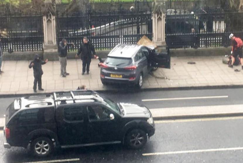 Warga Inggris berkumpul dekat sebuah mobil yang kecelakaan dan seseorang yang terbaring di tanah (kanan) di Bridge Street dekat Gedung Parlemen Inggris di London, Rabu (22/3). Terjadi serangan penusukan di dekat parlemen.