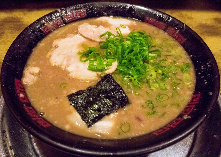 """大阪市では他に並ぶもののない、超濃厚豚骨スープが代名詞の有名ラーメン店です。その味を求める多くの人でいつも大行列ができており、食べれば絶対その理由に納得するはず。見た目非常に脂っぽく見えますが実はスープには脂不使用、この濃さはコラーゲンに由来するものなので、見た目よりもしつこさは感じないかと思います。いや、もっとこってり脂ギトギトがいいんだと言う方は、""""できるだけこってり・背脂ブロック""""と注文してみてください。濃厚スープ×背脂のド迫力に、昇天すること間違い無しです。"""