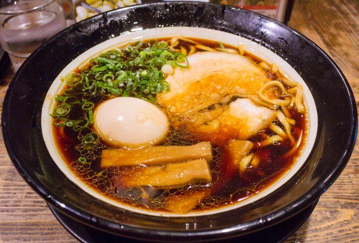 大阪ブラックと呼ばれる独特の真っ黒な醤油スープを武器に、某グルメサイトにて大阪のラーメンランキング3年連続1位に輝いたこともある名店です。大阪府内をはじめ京都や滋賀にも支店があり、その知名度は関西のラーメン屋ではトップクラスでしょう。見た目に反して味はそれほど濃くはなく、優しく主張するイカや海老が印象的。本店の営業時間は短いですが、梅田や道頓堀などの繁華街にある店舗は遅くまで営業しており、飲んだ後の〆にもオススメです。