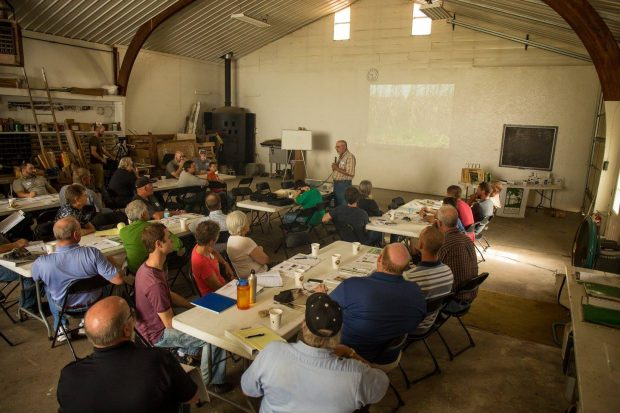 Would-be farmers attend a class in an experienced farmer's barn.