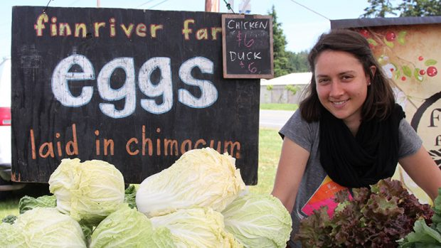A woman sells cabbages at a farmers market stand.