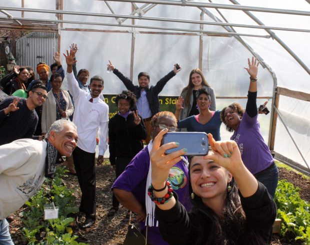 People stand in a greenhouse taking a fun selfie.