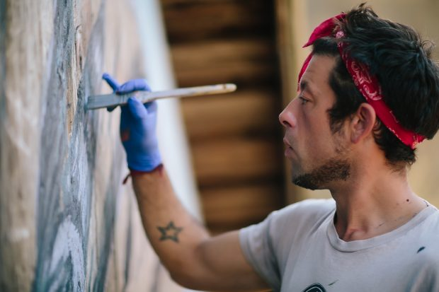 Artist Pete Hodapp, wearing a red bandana, painting his mural on the side of the barn.