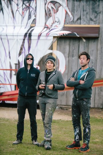 The artists Aaron Horkey, Malena Handeen, and Pete Hodapp stand in front of the Farm Art barn.