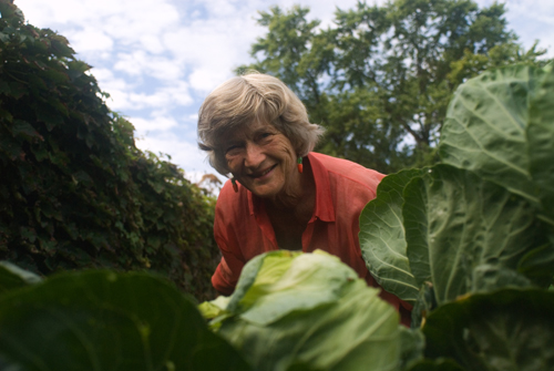 Joan Gussow peeks through a patch of cabbages in her garden.