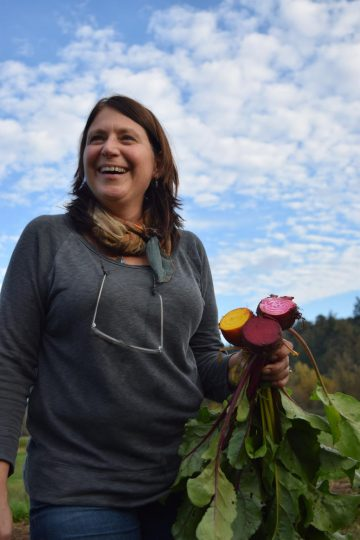 A woman holds three beets cut in half to show their vibrant red and yellow flesh.