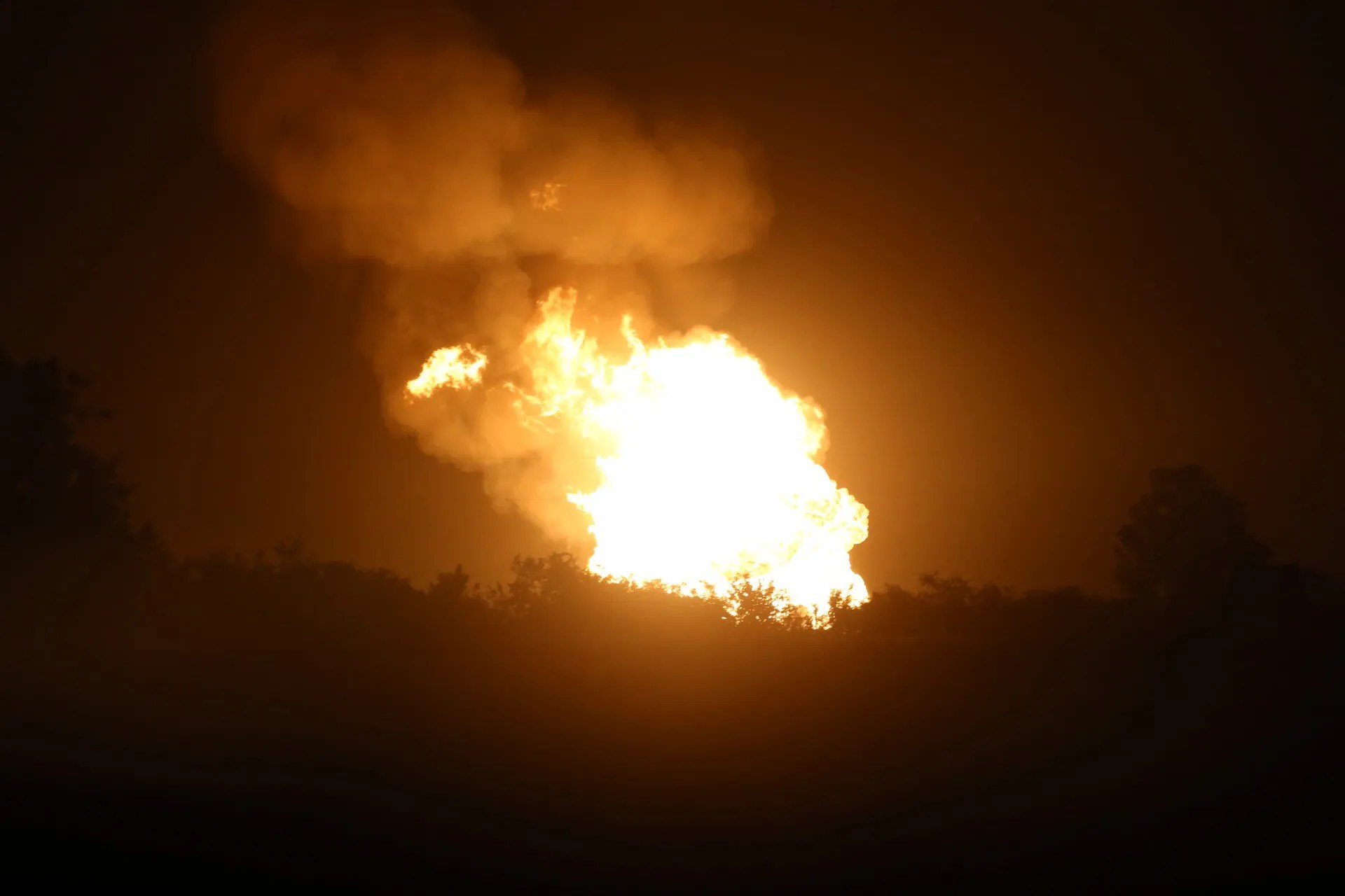 Fire after a pipeline explosion in rural DeWitt County, Texas, illuminates the horizon Sunday, June 14, 2015. Authorities said no one was injured after a natural gas pipeline rupture sparked a massive fire that prompted home evacuations in South Texas. (Richard Hoang/The Victoria Advocate via AP)