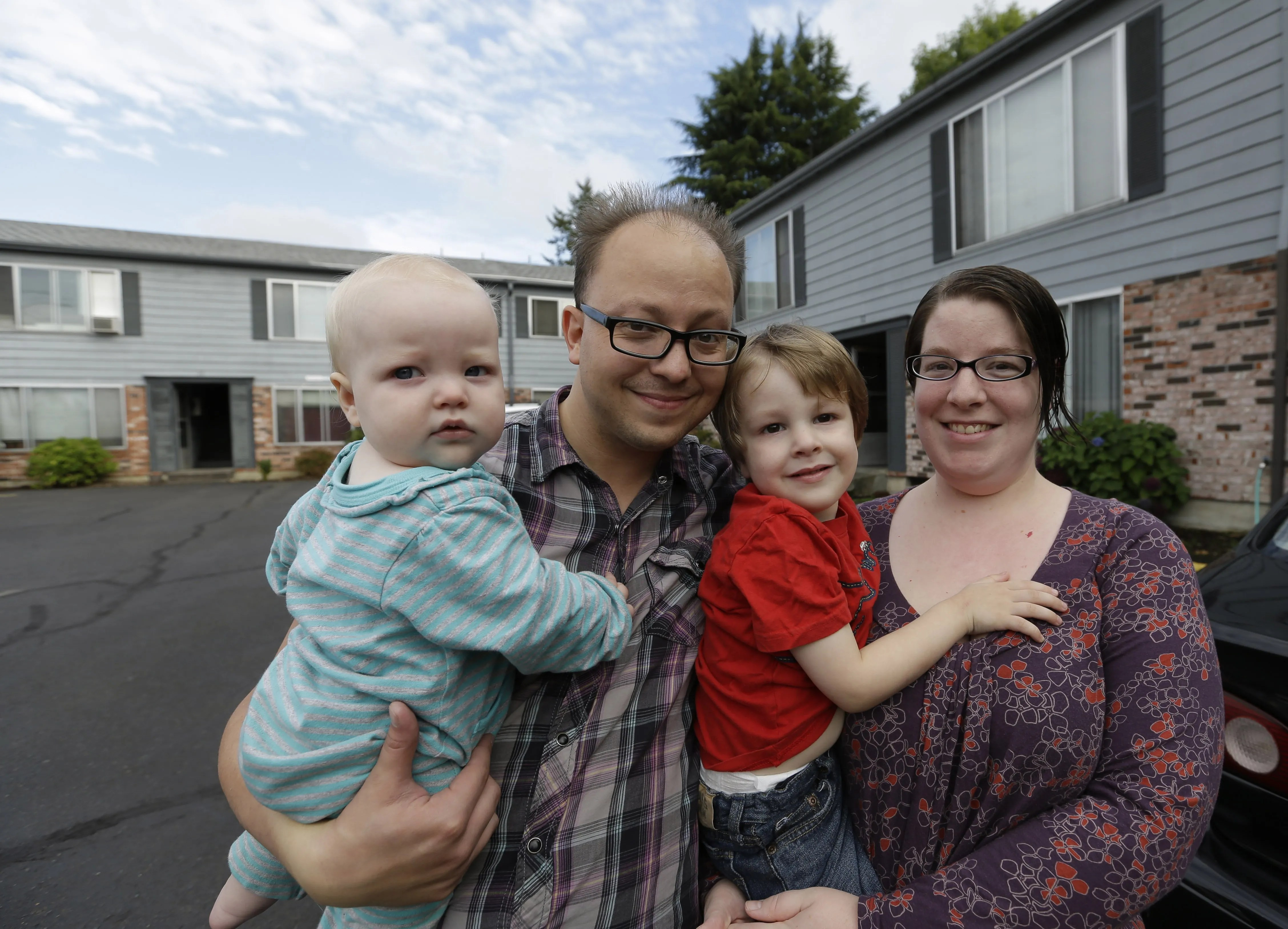 Steven and Nola Olsen in front of their Portland apartment building with Aubrielle, left, 1, and Marcus, 3. Steven Olsen had hoped to raise his two children in Portland, but a recent $200 rent increase is forcing them to move back to Missouri. (Don Ryan/The Associated Press)