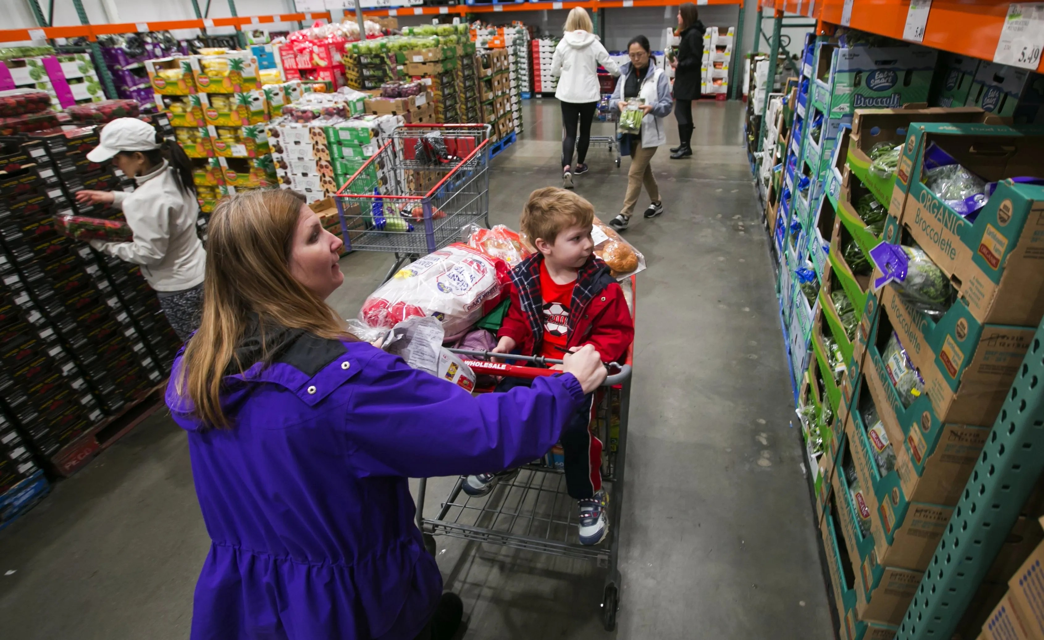 Kimberly Fee pushes a shopping cart holding her son, Cameron, 4, at Costco in Issaquah. Costco is working to boost its supply of organics. (Bettina Hansen/The Seattle Times)