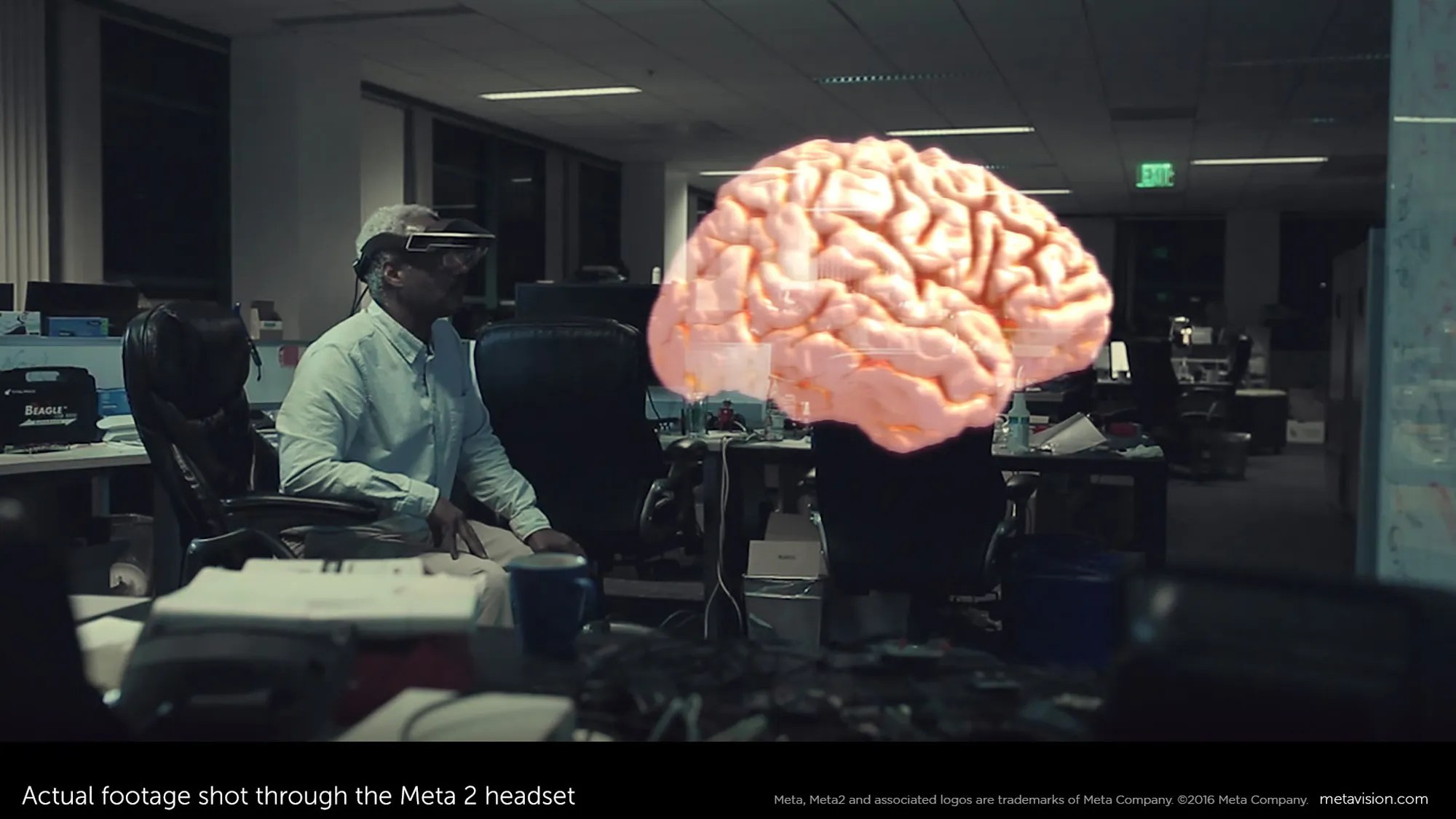 This February 2016 image provided by Meta shows actual footage of a model of a brain shot through the Meta 2 headset, while Meta employee Forest Rouse wears a Meta 2 headset, background left, in Redwood City, Calif.