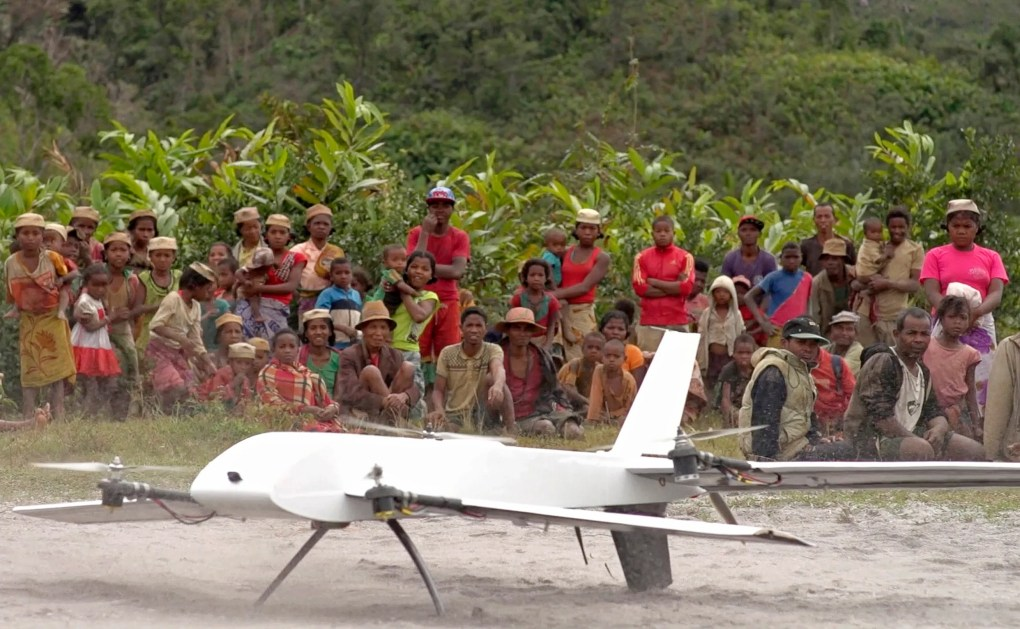 FILE – In this July 27, 2016, file frame from video provided by Vayu, Inc., residents from Ranomafana, Madagascar, watch before a drone containing medical samples takes off on a test flight from their remote village, which can only be reached on foot. (Stony Brook University/Vayu Inc. via AP, File)