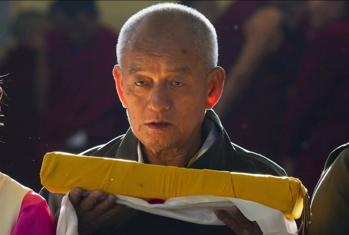 An exile Tibetan carries a ceremonial scarf and a religious text to offer to his spiritual leader the Dalai Lama at the Tsuglakhang temple in Dharmsala, India, Wednesday, Nov.