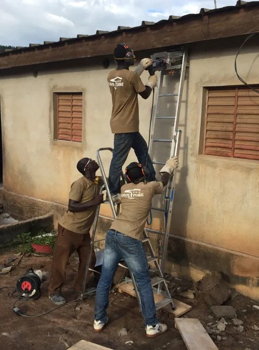 Workers drill holes along the roofline of a house in Kenya to install eave tubes to kill malaria-transmitting mosquitoes. In initial trials, mosquito populations in the village crashed.  (Penn State University)