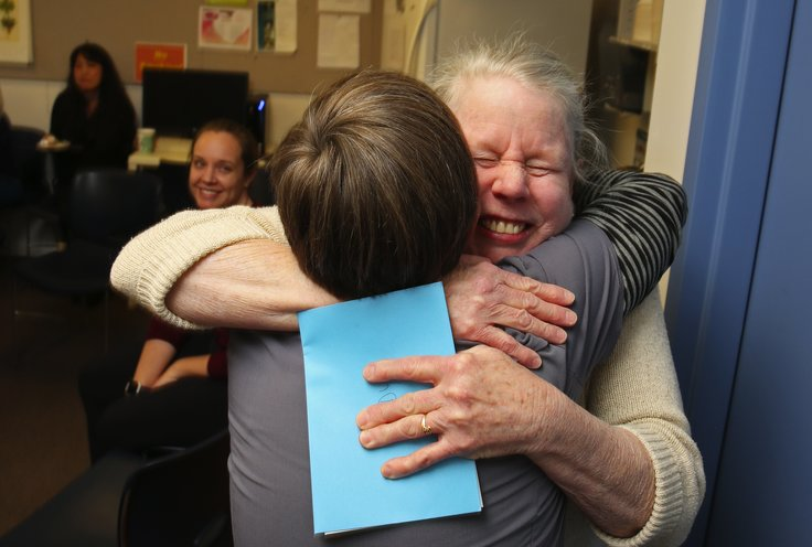 Wendy McNerthney, facing camera, who worked for more than 24 years at Bailey-Boushay House, hugs fellow registered nurse Hilary MacGregor at McNerthney's retirement party. (Ken Lambert/The Seattle Times)