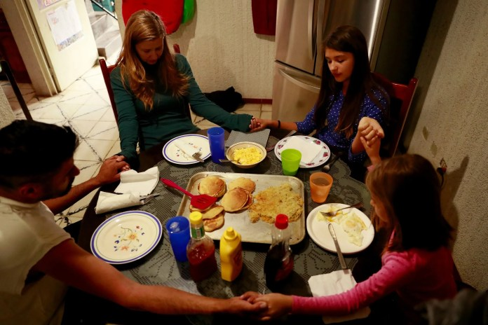 The family prays before a meal. It was breakfast for dinner, including pancakes. (Erika Schultz / The Seattle Times)