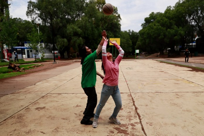 Chavo Eudave de la Torre plays basketball with his daughter Arianna at a Zacatecas park. On days he works, the two often play a game of basketball and eat at a nearby Little Caesars. (Erika Schultz / The Seattle Times)