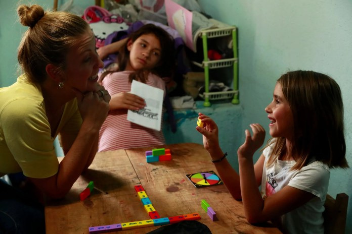 Inside Joy's store, she, Maya and Catalina play an English-language game of W-I-N-G-O, kind of a cross between Scrabble and Bingo. (Erika Schultz / The Seattle Times)