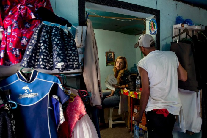 Joy and Rafael talk in the clothing shop in Zacatecas. It offers items from American thrift stores and Ross Dress for Less, including gowns, shoes and sunglasses. (Erika Schultz / The Seattle Times)