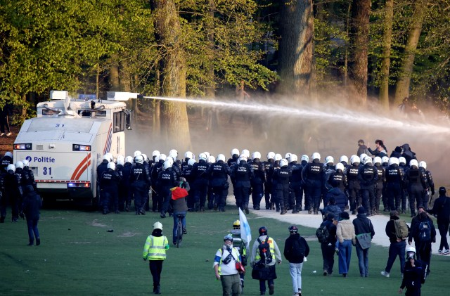 "Police use a water cannon against protesters at the Bois de la Cambre park during a party called ""La Boum 2"" in Brussels, Saturday, May 1, 2021. It was the second such open-air gathering in a month. (AP Photo / Olivier Matthys)"