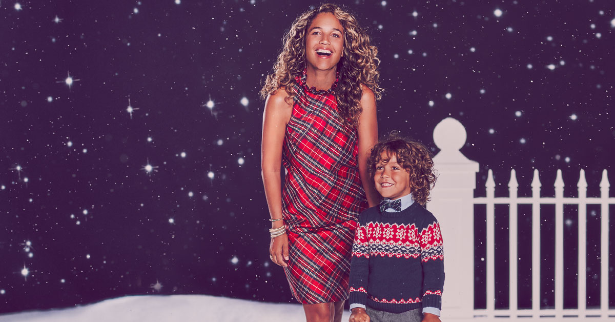 mother and son in holiday clothing at night stars by fence snow