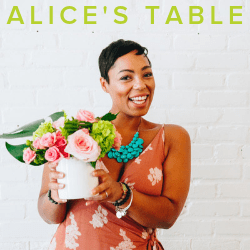 Advertisement photo for Alice's Table showing a woman holding a vase of flowers in front of a white wall.