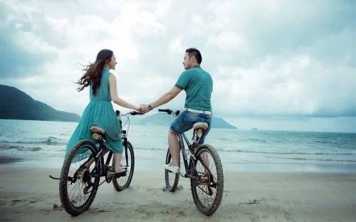 Casal de bicicleta na praia