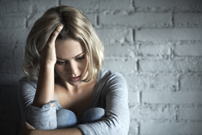 A pretty young blonde woman sitting down while looking severely depressed