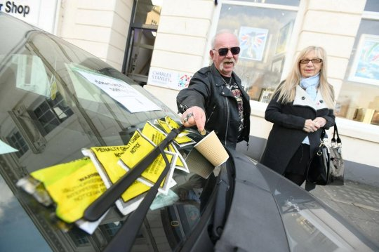 Ian McDonald and Jenny Revell show the abandoned Fiat some love. See SWNS story SWPLfine; Cheeky driver accepting donations to help pay for parking fines - after racking up hundreds of pounds in tickets. Cheeky motorist