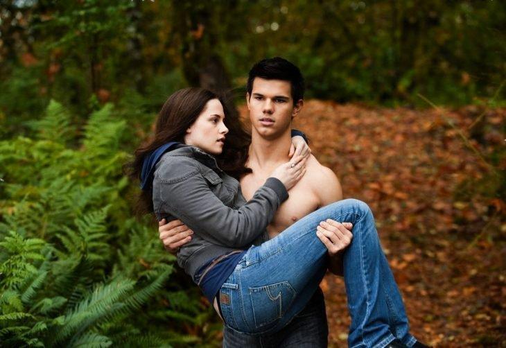 Chico musculoso carganco en brazos a una chica por el bosque
