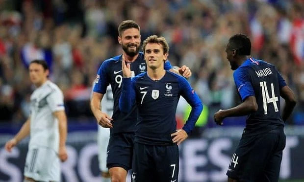 Griezmann celebrates his penalty finish with teammates Giroud and Matuidi