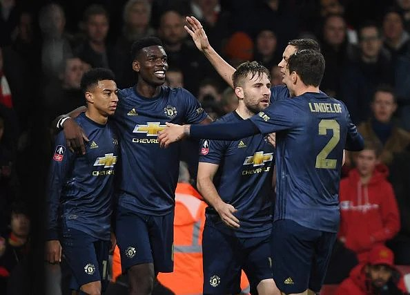 Pogba and Lingard (far left) celebrate with some of their teammates during a memorable fourth-round win