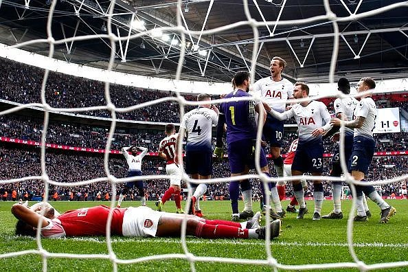 Tottenham players celebrate with Hugo Lloris after his penalty save to deny Aubameyang late on