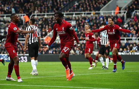 Divock Origi wheels away to celebrate his last-gasp effort, snatching all three points for Liverpool