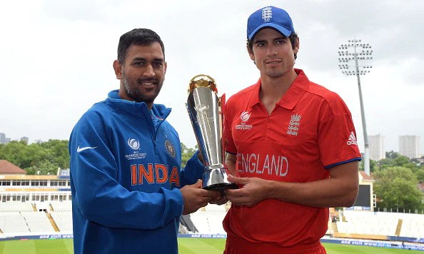 Indian captain Mahendra Sing Dhoni (L) and England captain Alistair Cook pose for photographs with the ICC Champions Trophy at Edgbaston in Birmingham, England on June 22, 2013 a day ahead of the 2013 ICC Champions Trophy Final cricket match between England and India. AFP PHOTO/Paul ELLIS - RESTRICTED TO EDITORIAL USE        (Photo credit should read PAUL ELLIS/AFP/Getty Images)