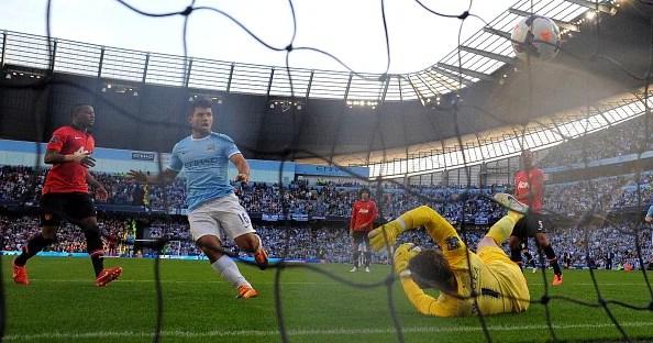 Manchester City's Argentinian forward Sergio Aguero scores his team's third goal past Manchester United's Spanish goalkeeper David de Gea