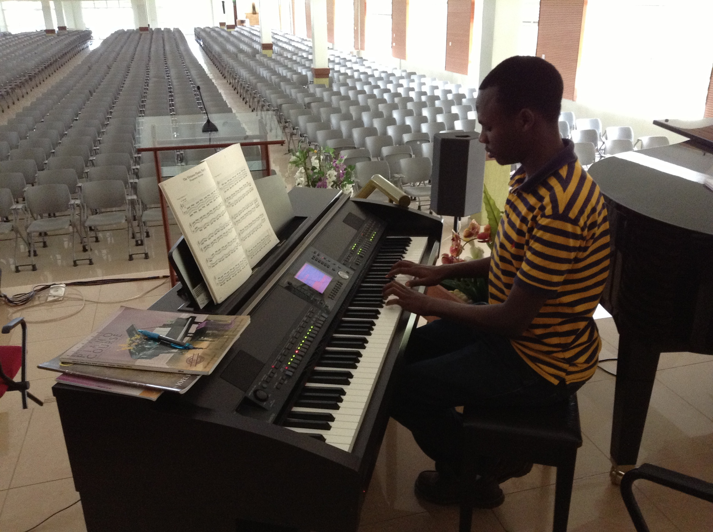 Eric completely surprised me when I met him. He has taught himself over the years to read music and is very good at playing by ear. So far, Eric is the only Rwandan I've met who has a good understanding of written notation. He is the most advanced student I get to teach and now regularly plays at the University for Church service. Here we are going over some virtuosic piano techniques.