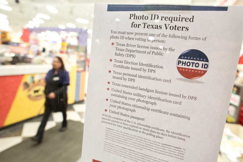 A sign describing Texas' new voter ID law is displayed at Fiesta Mart in Austin on Election Day 2013.