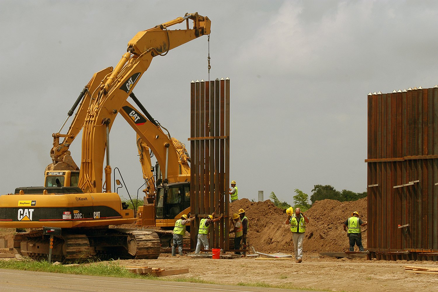 A construction crew works to erect a portion of the border wall along Oklahoma Ave. south of Brownsville on June 9, 2009.