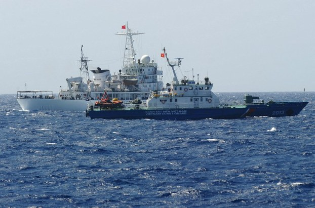 A Chinese coast guard ship (back) sails next to a Vietnamese coast guard vessel (front) near China's oil drilling rig in Vietnam's exclusive economic zone in the South China Sea, May 14, 2014.