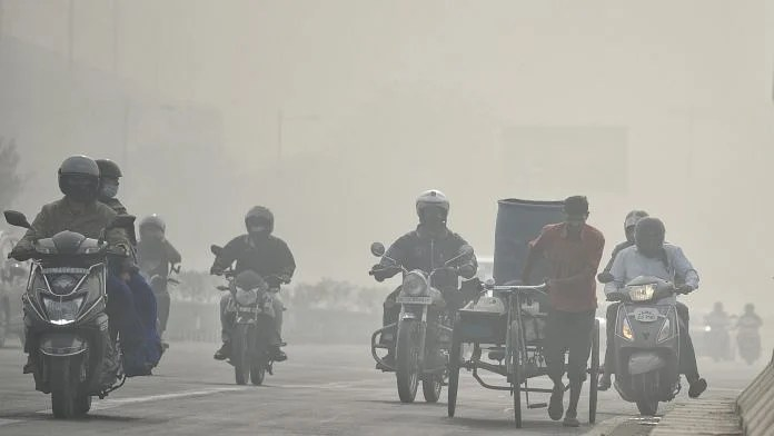 Commuters on two-wheelers plying through a thick layer of smog in New Delhi on 10 November | ANI Photo
