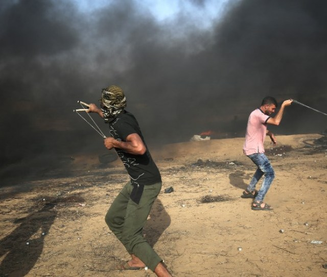 Palestinian Demonstrators Use Slingshots To Hurl Rocks At Israeli Forces During Clashes Along The Border With