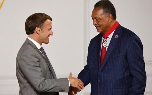 Le président français Emmanuel Macron serre la main du révérend Jesse Jackson (à droite), militant américain des droits civiques, après lui avoir décerné la Légion d'honneur à l'Elysée, à Paris, le 19 juillet 2021. (Crédit : Ludovic MARIN / POOL / AFP)