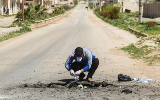 A Syrian man collects samples from the site of a suspected toxic gas attack in Khan Sheikhoun, in Syria's northwestern Idlib province, on April 5, 2017. (AFP/Omar Haj Kadour)