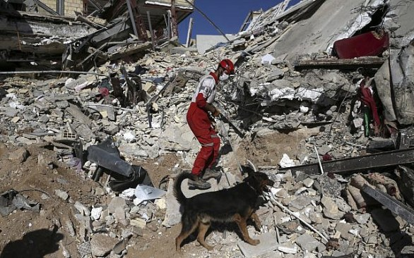 A rescue worker searches the debris with his sniffing dog on the earthquake site in Sarpol-e-Zahab in western Iran, Tuesday, November  14, 2017. (AP Photo/Vahid Salemi)